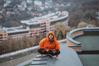 Woman practicing yoga on the roof and doing yoga exercises