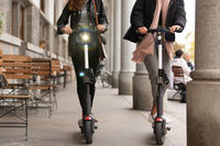 Unrecognizable trendy fashinable teenager girls riding public rental electric scooters in urban city environment. New eco-friendly modern public city transport in Ljubljana, Slovenia