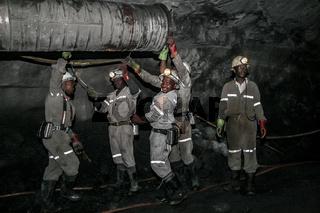 Underground Platinum miners fitting a ventilation pipe