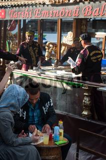 A Turkish couple eating a fish sandwich the famous street food Balik Ekmek beside the Golden Horn, I