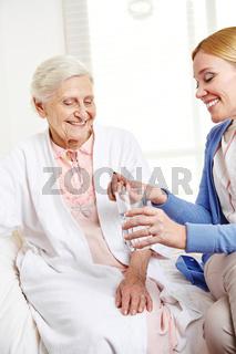 Frau bietet Seniorin eine Tablette an
