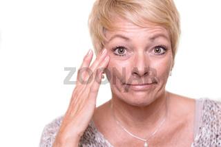 Attraktive blonde Frau überprüft ihre Haut