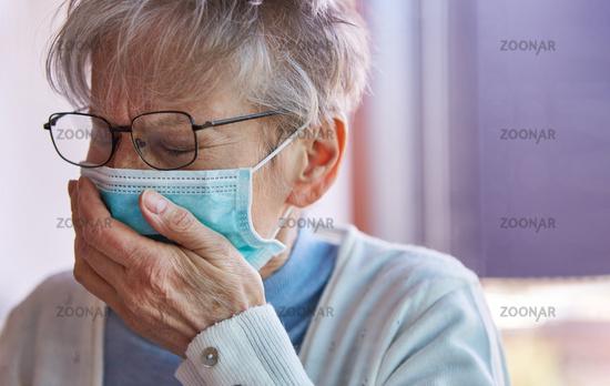 Seniorin mit Mundschutz hustet in ihre Hand