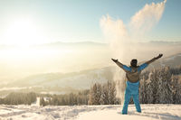 Happy Man standing in deep snow throwing snow into sunrise sunlight. Beautiful Winter Mountain Landscape. Allgau, Bavaria, Alps, Germany.