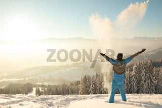 Happy Man standing in deep snow throwing snow into sunrise sunlight. Beautiful Winter Mountain Landscape. Allgau, Bavaria, Alps, Germany.