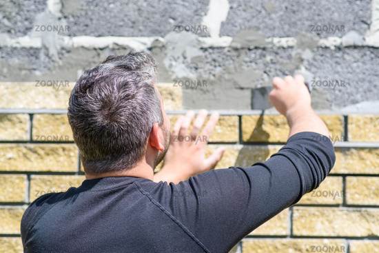 Man decorates the facade of the fence with decorative torn bricks. Work at home during quarantine