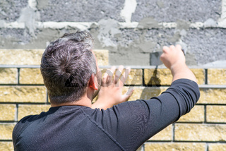 Man decorates the facade of the fence with decorative torn bricks. Work at home during quarantine. Do it yourself