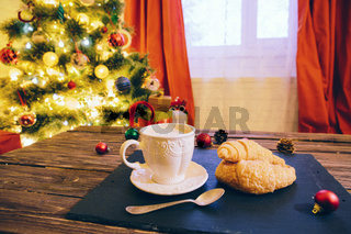 Mug with hot chocolate on a wooden table with Christmas decorations on a background of the Christmas tree