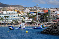 Tenerife, Spain - October 15, 2019: People enjoy water amusements on the Los Cristianos coastline, touristic town, situated on south coast of Canary Islands, Spain