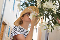 Beautiful young caucasian woman smelling white flowers on the street of traditional old Mediterranean costal town