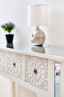 Living room detail design stylish luxury furniture floral ornate carving art of bedside table violet flower potted plant and lamp on it, selective focus. Background element close up view, no people
