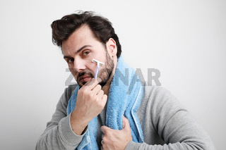 Bearded man shaving with razor in the morning. Isolated over white background.