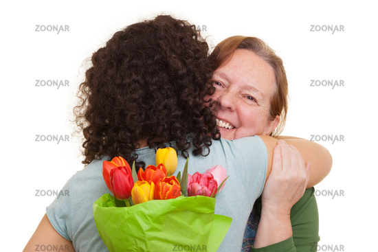 Young woman with tulips hidden behind her back hugging elderly woman, isolated on white background. Mothers day, Valentines day, Easter and surprise Concept.