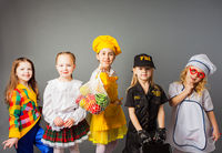 Happy schoolgirls in costumes of different professions isolated on grey background.