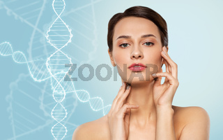 young woman touching her face over dna molecules