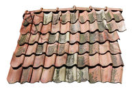 Fragment of a broken clay tiled roof of a village barn isolated