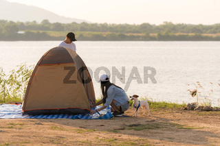 Young adult Asian couple pitch and set up tent for camping
