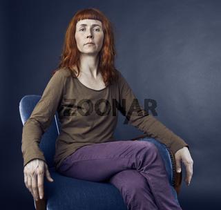 Frau in Sessel überlegen aussehend