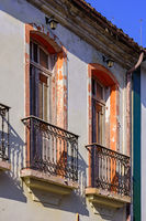 Window of old colonial style house with balcony and colorful frame