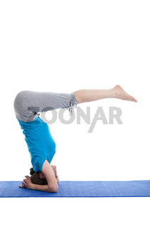 Yoga - young beautiful woman  yoga instructor  doing Lowered Bound Headstand (Salamba sirsasana with Urdhva Dandasana) exercise