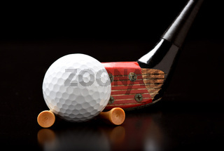 An Antique Fairway Wood with a golf ball and tees on black with reflection.