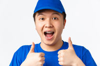 Online shopping, fast shipping, employees and home delivery concept. Close-up of excited happy asian male courier in blue uniform, showing thumbs-up and looking amused, white background