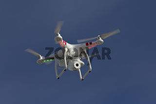 small unmanned helicopter with a camera floating in the blue sky