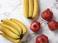 ripe red pomegranates and yellow bananas on a white marble table