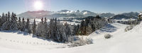 panoramic landscape in winter wirh mountain range and sun on sky