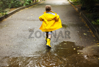 Little girl wearing yellow boots in rainy day