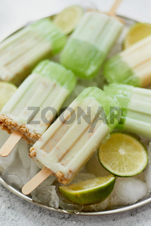Summer refreshing homemade lime popsicles with chipped ice over stone background