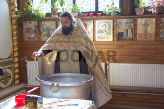 Belarus, Gomel, September 17, 2018. Prudkovsky church. The baptism of the child. Orthodox priest blesses the font for baptism.