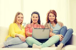 three smiling teenage girls with laptop at home
