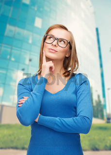 happy woman in black eyeglasses dreaming