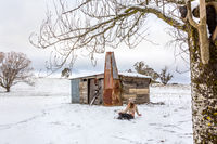 Woman relaxing in snowy field with old rustic barn