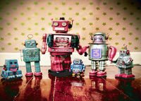 A family of retro robot toys on old wooden