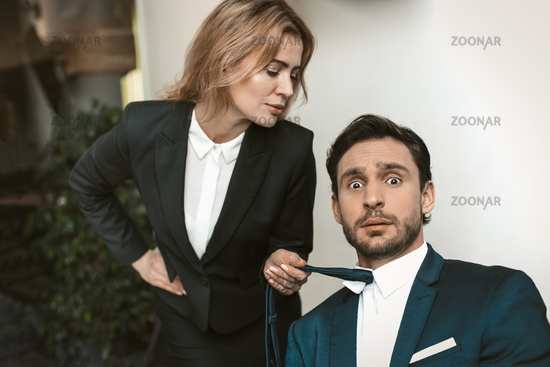 Pretty businesswoman seduces her male boss or collegue. Caucasian female holding tie of businessman. Sexual harassment concept