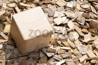 Wooden cube lying on mulch