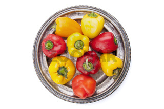 Colored peppers on silver plate
