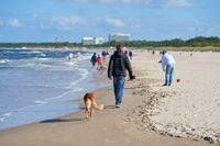 Tourists walking on the beach of Swinoujscie on the Polish coast of the Baltic Sea