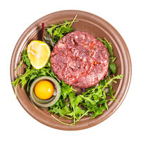 top view of Steak tartare portion on brown plate