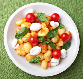 Homemade gnocchi with tomato sauce basil and mozzarella.