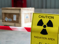 Radiation warning sign on the area warning tape around the Dangerous material package in the factory