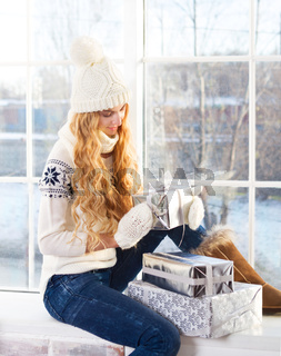Young happy blond woman looking at Christmas presents