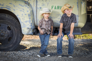 Two Young Boys Wearing Cowboy Hats Leaning Against Antique Truck