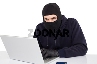 Hacker in balaclava hacking a laptop