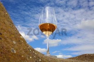 Glas mit Rosé Wein auf einem Stein