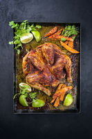 Traditional barbecue spatchcocked chicken al mattone chili with sweet potato chips and limes offered as top view on an old rustic metal tray