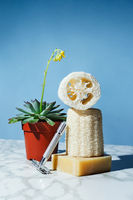 Eco friendly loofah sponges with homemade soap bars and reusable razor on a marble, sustainable bath and home concept, selective focus