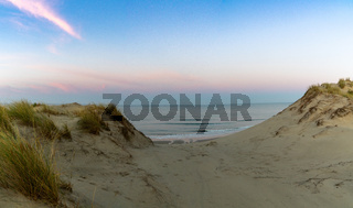 A wild coast and ocean with large sand dunes at sunrise